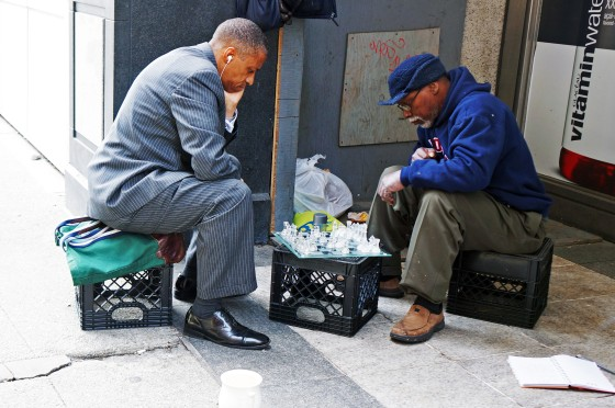 Businessman playing chess with homeless man